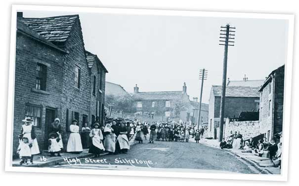 This view looking up the High Street in Silkstone shows a number of buildings which have changed relatively little over the years, apart from, of course, the groups of people who are gathered in the street posing for the photographers.