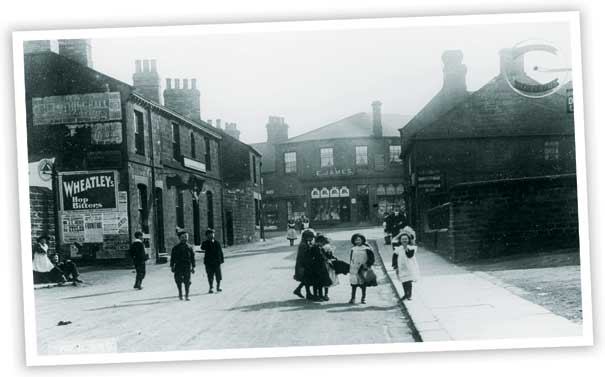 This view looking along High Street, Hoyland shows the old Post Office building. The increase in motor traffic means that the area is now subject to a one-way system. The older buildings on the left hand side of the photo have been replaced.